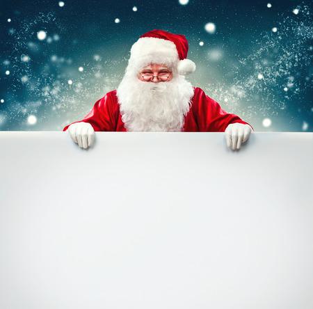 Foto de Santa Claus holding blank advertisement banner background with copy space - Imagen libre de derechos