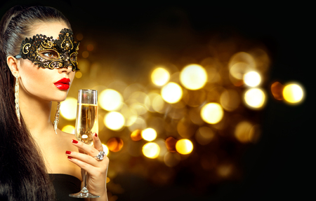 Foto de Sexy model woman with glass of champagne wearing venetian masquerade mask - Imagen libre de derechos