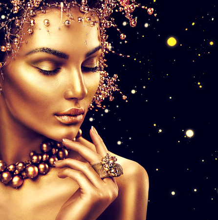 Photo pour Beauty fashion model girl with golden skin, makeup and hairstyle isolated on black background - image libre de droit
