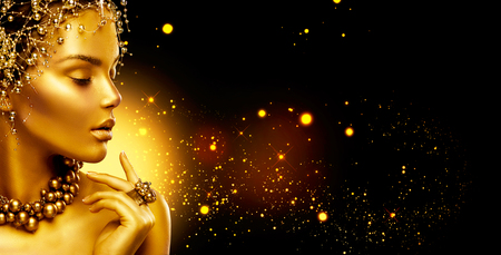 Photo pour Golden woman. Beauty fashion model girl with golden make up, hair and jewellery on black background - image libre de droit