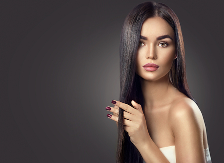 Photo for Beauty brunette model girl touching long healthy hair - Royalty Free Image