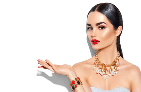 Photo pour Sexy young woman with perfect makeup and trendy golden accessories showing empty copy space on the open hand palm - image libre de droit