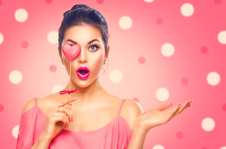 Foto de Valentine's Day. Beauty surprised young fashion model girl with Valentine heart shaped cookie - Imagen libre de derechos