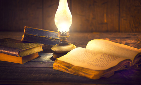 Foto de Old books and vintage oil lamp. Kerosene lantern and open old book on wooden table - Imagen libre de derechos