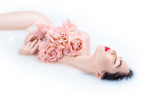 Photo pour Beautiful Fashion model girl with bright makeup and pink roses taking milk bath, spa and skin care concept - image libre de droit
