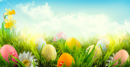 Foto de Easter nature spring scene background. Beautiful colorful eggs in spring grass meadow - Imagen libre de derechos