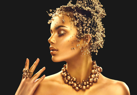 Foto de Gold woman skin. Beauty fashion model girl with golden makeup, hair and jewellery on black background - Imagen libre de derechos