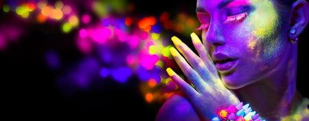Foto de Beauty woman in neon light, portrait of beautiful model with fluorescent makeup - Imagen libre de derechos