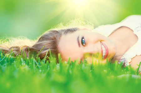 Photo pour Beautiful teenage girl lying on green grass outdoor - image libre de droit