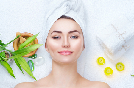 Photo for Spa woman applying facial mask. Closeup portrait of beautiful girl with a towel on her head applying facial clay mask - Royalty Free Image