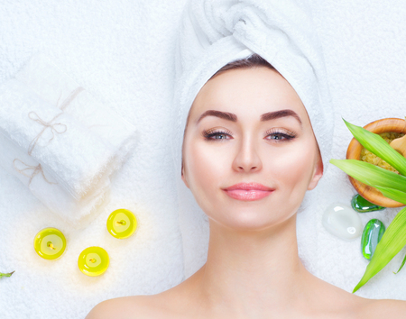 Photo pour Spa woman applying facial mask. Closeup portrait of beautiful girl with a towel on her head applying facial clay mask - image libre de droit