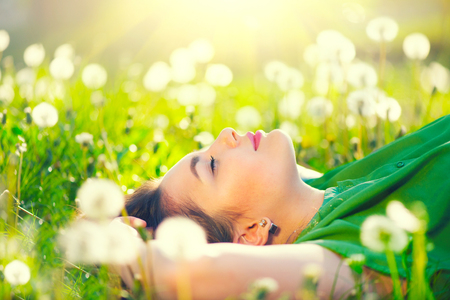 Foto de Beautiful young woman lying on the field in green grass and dandelions - Imagen libre de derechos