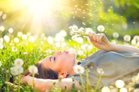 Photo pour Beautiful young woman lying on the field in green grass and blowing dandelion - image libre de droit
