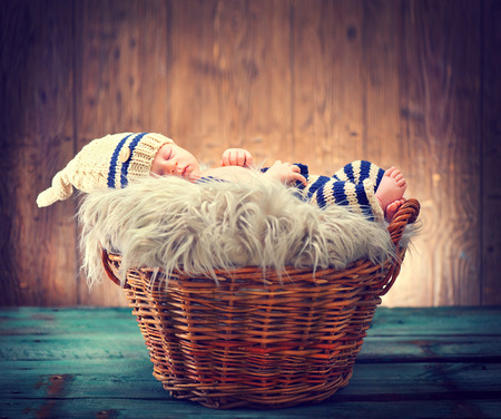 Photo pour Two weeks old infant baby wearing knitted funny costume, sleeping in a basket over wooden background. Sweet newborn baby portrait - image libre de droit