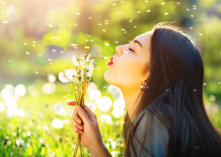 Photo pour Beautiful young woman blowing dandelions and smiling - image libre de droit
