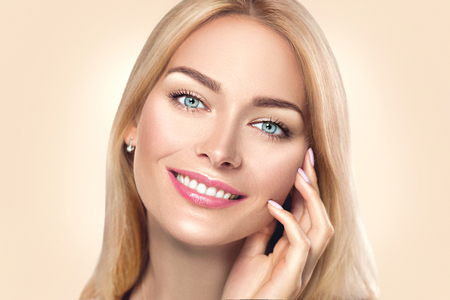 Foto per Beauty spa woman touching her face and smiling. Skincare concept - Immagine Royalty Free