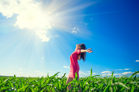 Foto de Beauty girl on summer field rising hands over blue clear sky. Happy young healthy woman enjoying nature outdoors - Imagen libre de derechos