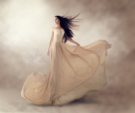 Foto de Fashion model in beautiful luxury beige flowing chiffon dress - Imagen libre de derechos