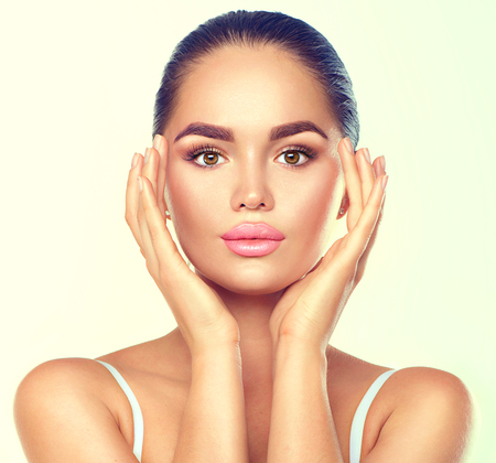 Foto de Beauty brunette spa woman with perfect makeup touching her face. Skincare concept - Imagen libre de derechos