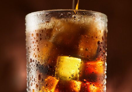 Photo pour Cola pouring in glass with ice cubes over dark background - image libre de droit