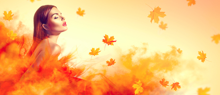 Photo for Beautiful fashion woman in autumn yellow dress with falling leaves posing in studio - Royalty Free Image