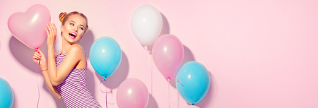 Foto de Beauty joyful teenage girl with colorful air balloons having fun over pink background - Imagen libre de derechos