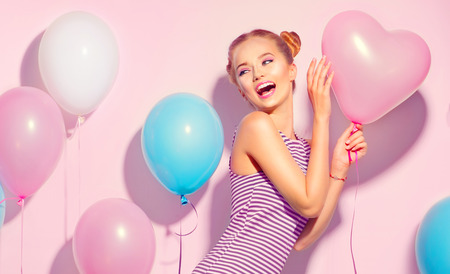 Photo pour Beauty joyful teenage girl with colorful air balloons having fun over pink background - image libre de droit