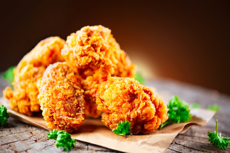 Photo for Fried chicken wings and legs on wooden table. Closeup of tasty fried chicken - Royalty Free Image