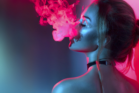 Foto de Fashion art portrait of beauty model woman in bright lights with colorful smoke. Smoking girl - Imagen libre de derechos