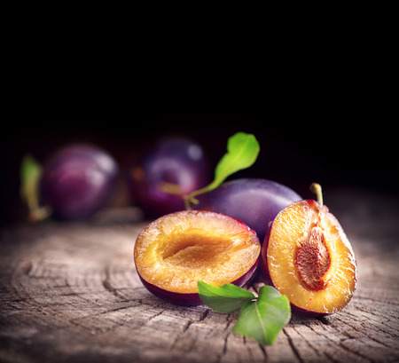 Foto de Plum. Juicy ripe organic plums closeup, over wooden background - Imagen libre de derechos