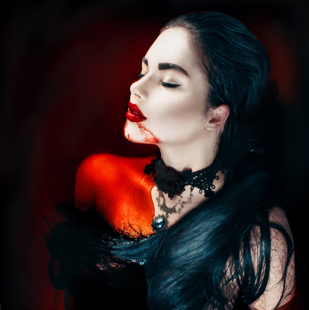 Foto de Beauty Halloween sexy vampire woman with dripping blood on her mouth - Imagen libre de derechos