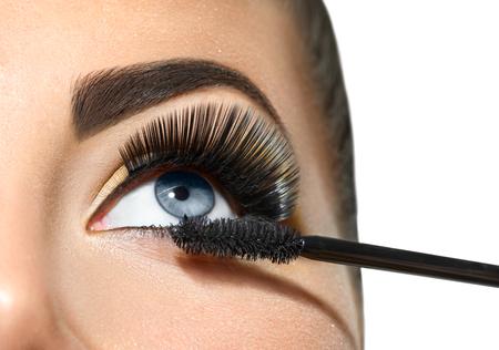 Photo pour Long lashes closeup. Beautiful woman applying mascara on her eyes. Makeup - image libre de droit