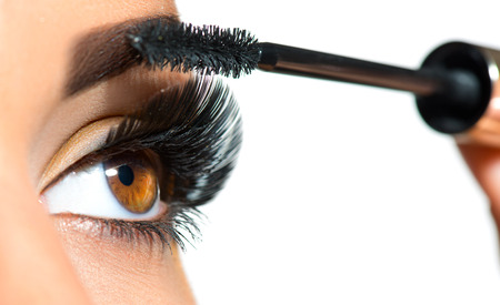 Photo pour Long lashes closeup. Beautiful woman applying mascara on her eyes. Makeup - image libre de droit