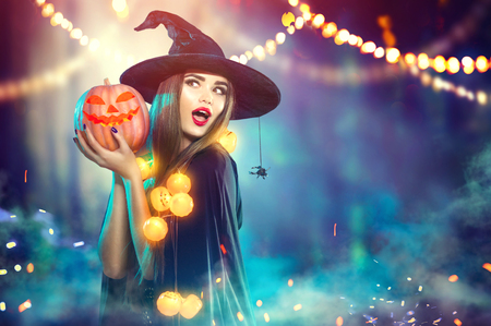 Foto de Halloween. Witch with a carved pumpkin and magic lights in a dark forest - Imagen libre de derechos