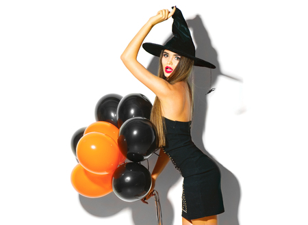 Photo for Halloween party girl. Sexy witch holding black and orange air balloons. Beautiful young woman in witches hat and costume - Royalty Free Image