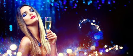 Photo pour Sexy model girl drinking champagne over holiday glowing background - image libre de droit