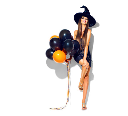 Foto de Halloween party girl. Sexy witch holding black and orange air balloons. Beautiful young woman in witches hat and costume - Imagen libre de derechos