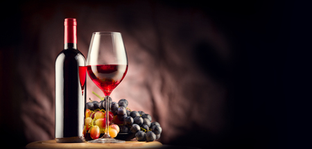 Photo pour Wine. Bottle and glass of red wine with ripe grapes still life - image libre de droit