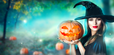 Foto de Halloween witch with a carved pumpkin and magic lights in a dark forest - Imagen libre de derechos