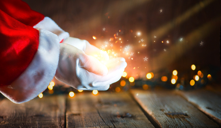 Photo pour Christmas scene. Santa Claus showing glowing stars and magic dust in open hands. Proposing product - image libre de droit
