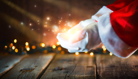 Foto de Christmas scene. Santa Claus showing glowing stars and magic dust in open hands. Proposing product - Imagen libre de derechos