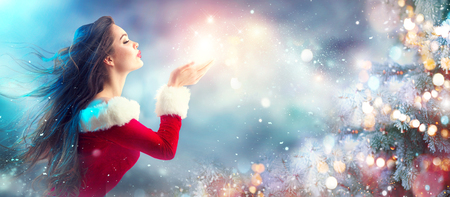 Photo pour Christmas scene. Sexy Santa. Brunette young woman in party costume blowing snow over holiday blurred background - image libre de droit