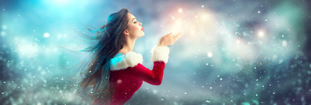 Photo for Christmas scene. Sexy Santa. Brunette young woman in party costume blowing snow over holiday blurred background - Royalty Free Image