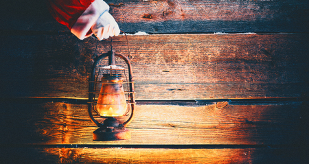 Photo pour Christmas scene. Santa Claus hand holding vintage oil lamp over holiday wooden background - image libre de droit