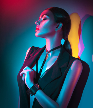 Foto de Portrait of sexy young woman in black clothes, fashion accessories, bright makeup in neon light - Imagen libre de derechos