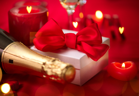 Photo for Valentine's Day romantic dinner. Date. Champagne, candles and gift box over holiday red background - Royalty Free Image