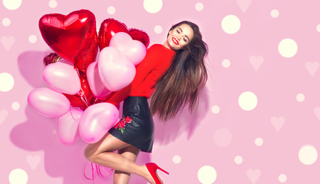 Foto de Valentine's Day. Beauty girl with colorful air balloons having fun over pink background - Imagen libre de derechos