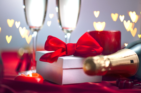 Foto de Valentine's Day romantic dinner. Champagne, candles and gift box over holiday background - Imagen libre de derechos