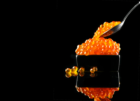 Photo pour Caviar in a spoon. Salmon caviar in a bowl over black background. Closeup trout caviar - image libre de droit