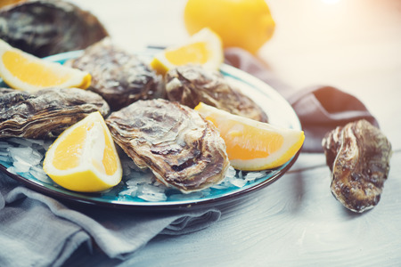 Foto de Fresh oysters close-up on blue plate, served table with oysters, lemon in restaurant. Gourmet food - Imagen libre de derechos